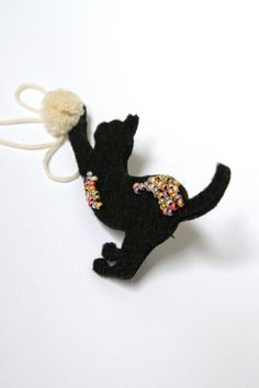 I have been observing my cat playing with a ball of yarn and I had an idea of creating this charming cat brooch. I cut out a cat silhouette in a black thick felt and embroidered it with beads in beautiful harmonious colors : pastel purple, pink, gray, silver, golden. The ball the cat is