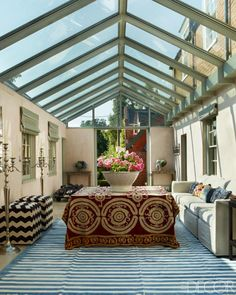 The conservatory features a custom sofa, an antique suzani purchased in Paris, and a kilim and ottomans by Irving & Morrison.