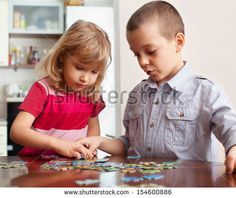 Children, playing puzzles at home - stock photo