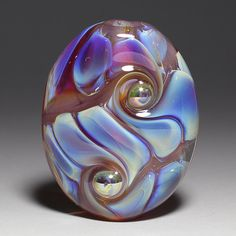 This pressed focal bead has a core of soft violet encircled by rippling pleats of color shifting silver glass. Metallic glass swirl dots have been