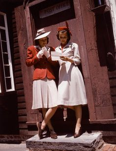 """""""Two models in hats standing on front step, one is wearing ared plaid jacket with a beige wool skirt, and the other is wearing wool dress with a red dickey, 1940."""""""