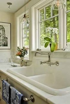 farmhouse kitchen...reminds me of the big cottage...love the windows, marble, huge sink, art