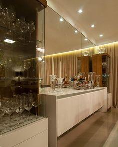 Para a sala de jantar, optamos por uma composição simétrica com duas torres de cristaleira em madeira e branco, e um buffet central. O espelho valoriza e enobrece o ambiente. #porTrennaArquitetura   Padrão Trenna Arquitetura