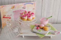 Miniature Cupcakes With Pink Roses On A Covered Decorative Ribbed Glass Cake Stand, A Glass Bowl Of Icing, And Cupcakes In The Making by LittleThingsByAnna