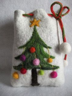 """Kleiner Filzbeutel """"Tannenbaum"""" Weihnachten *Schöner kleiner Filzbeutel aus weißer und hellgrauer Merinowolle für die Aufbewahrung von Kleinigkeiten oder als weihnachtliche Geschenkverpackung.* Der Filzbeutel ist mit einer Tanne und vielen bunten Kugeln verziert. Auf der Tannenspitze prangt ein goldverzierter Stern. Goldene Stickereien machen aus dem Filzbeutel ein echtes Schmuckstück. Der Beutel wird mit einer Filzkordel geschlossen, an deren Enden gefilzte Bommeln baumeln."""