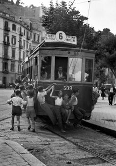 These young Neapolitans like the danger of the strictly-forbidden    practise of hanging onto the backs of street cars, Naples, 1948    photo by David Seymour