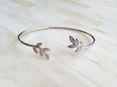 Gorgeous Autumn leaves bangle. Perfect for stacking or by itself. Perfect for anyoccasion or for everyday wear! Also, these bangles are perfect for the Autumn season!Give yourself a dosage of sparkle and beauty with this bracelet. Featuring gold/silver-toned slim copper band with leaves charm. It is a stunning piece to add instant style to any outfit.  Hurry! Only 3 Available! Colors: Gold and Silver Should fit most wrists   Have ANY questions? Feel free to contact us at ANYTIME!