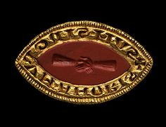 Gold seal , the pointed oval mount set with a red jasper intaglio of two hands clasped in friendship, surrounded by a Latin inscription in Lombardic script: + SUM SINGUM AMORIS, translating I am the sign of love. At the back of the mount, behind the cross marking the beginning of the inscription there is a suspension loop. Mount and gem 13th century.