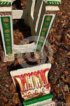 BUDDHIST and ANIMIST ASIAN SPIRIT HOUSES: Medium Close Up 2-Shot View of Pedestals used to support local spirit houses in Southeast Asia, lying in a field amongst dry leaves near a hoiy site. They are painted with gold, green, and red accent paint