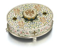 A FABERGÉ PARCEL-GILT SILVER AND CLOISONNÉ ENAMEL INKWELL, MOSCOW, 1899-1908 oval, surface decorated with scrolling shaded flowers and leaves on cream grounds, the raised central pot with hinged lid painted with an Imperial eagle above a chevron and swirl neck