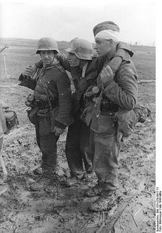 1944 Russia, wounded German soldier with his mates in the mud