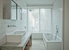 The master bath is a clean and spare space, a mixture of white and concrete