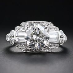 A consummate late-Art Deco platinum and diamond engagement ring blazing front and center with a gorgeous and glistening transitional European\/round brilliant-cut diamond weighing just a handful of points shy of 2.00 carats.