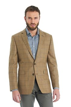 This men's Blazer tailored fit camel with navy windowpane jacket is single breasted with two button fastening.  This wool jacket has two straight pocket flaps on the front, brown elbow patches, a detachable collar tab and three internal pockets.  Wear with jeans or chinos to complete your smart casual look.