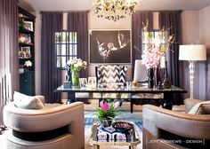 Grey walls, dark grey curtains, silver chandelier, black and white printed chair, clear desk, grey chairs, white lamp, and black and white wall art