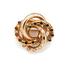 Two-Color Gold, Diamond, Ruby and Sapphire Circle Brooch   14 kt. yellow & rose gold, 7 diamonds ap. .55 ct., c. 1940, ap. 12.8 dwt.
