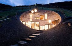 Always wanted an home bunkered in the side of a hill.  Like the oval entry and random rectilinear window contrast.