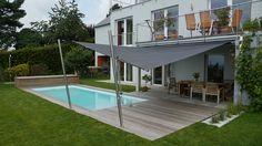 Diese Poolumrandung mit kleiner Terrasse wurde mit einer Soliday CS Anlage ausgestattet, welche die bestehende Beschattung ideal ergänzt und somit ausreichend Schatten für alle Badegäste bietet. In der gegenüberliegenden Holzbox ist die Schwimmbadabdeckung raffiniert verstaut.