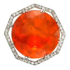 Edwardian Fire Opal Diamond platinum Ring. An Edwardian Fire Opal and Diamond Ring, designed around a circular-cut fire opal, weighing approximately 14.5-15 carats, within a frame of old European-cut diamonds, mounted in platinum, circa 1910.