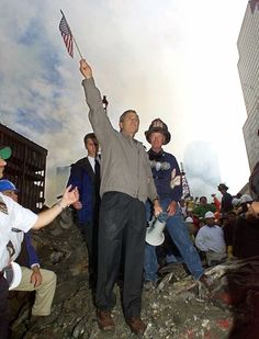 As rescue efforts continue in the rubble of the World Trade Center in New York, President Bush raises an American flag while standing on a burnt fire truck in front of the World Trade Center during a tour of the devastation, Friday, Sept. 14, 2001.