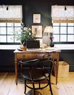 Small home office with dark walls, pale curtains and wooden furniture.