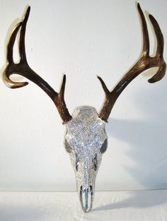 This deer skull has been painted with silver leaf paint then embellished with thousands of brilliant crystal rhinestones that have been hand