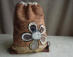 UPCYCLED~~REPURPOSED~~DRAWSTRING CINCH SACK BACK PACK in a Warm Neutral Color Palette. The front has a structured swirl design that has really