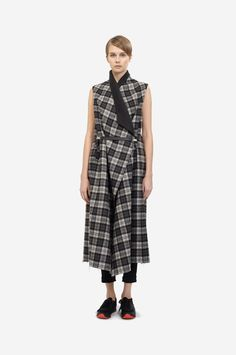 LONG PLAID VEST Shorthaired model wearing a black & grey checkered wool vest with a minimalistic leather clip belt and black sneakers. Design: Lucie Kutálková / LEEDA