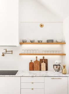 Stacked oak floating shelves are mounted to white herringbone backsplash tiles beside a white hood fixed above a brass swing arm pot filler. An induction cooktop is fitted to a white and gray quartzite countertop complementing white flat front cabinets and drawers finished with brass hardware.