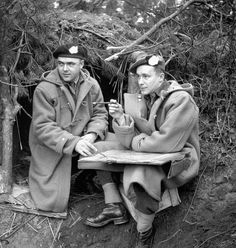 Captain D.N. McDonald, 12th Manitoba Dragoons, and Major R.B. MacNeill, The Queen's Own Cameron Highlanders of Canada, working outside a dugout in the Hochwald, Germany, ca. 10 March 1945