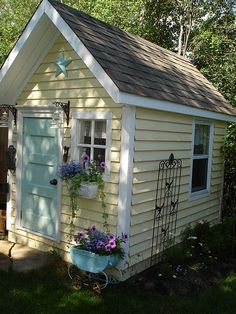 found this while googling ideas for the girls' playhouse. I love the color of the house and the door. Even the little planter.