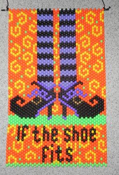 This is a If The Shoe Fits Witch Legs and Shoes Halloween Beaded Banner with black nylon cord for hanging Finished Size is: 12 wide x 19 long. without hanger Size with Cord Hanger: 12 wide x 31 high Cord Hanger can be shortened. Handmade with opaque plastic pony beads in colors of Black, Orange, Yellow, Green, Purple, Lilac, and nylon thread Can be hung outside or inside. A Great Decoration for Halloween. . This Banner is ready to ship Can be bought complete or as a kit