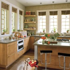Light-filled #Kitchen | Because there's a bevy of surrounding windows that also contain a lot of mullions, upper cabinetry would have competed with this look. Tiers of cantilevered shelves get the job done.