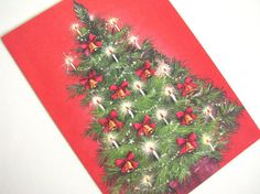 Vintage holiday Christmas card - unused. With a bold red background, this cheerful Christmas tree is lit with candles and hung with bells.
