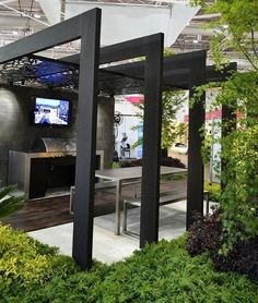 The intricate etched metal shade adds glamour to the edgy solid black pergola and silver furniture.