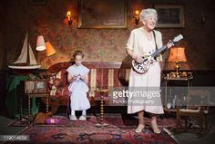 Bildbanksbilder : Older woman playing guitar as girl knits