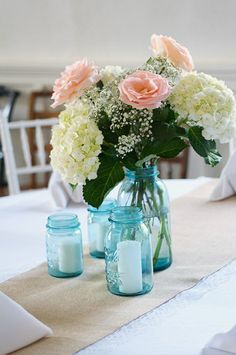 Blue mason jars, great contrast with the super feminine flowers