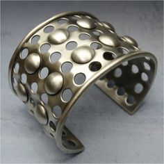A silver cuff with a geometric pattern made using Swanstrom Round Disc Cutter