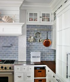 blue tile backsplash with pot rack. Kitchen