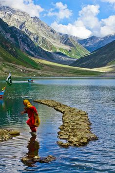 Risky business  At lake Saif-ul-Maluk, Kaghan, Pakistan.  A local girl hopping over stones to reach ashore after a boat ride with her friends.