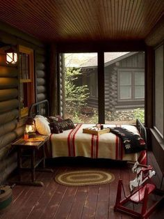 Antique metal bed with Pendleton or Hudson Bay Blankets in screened porch