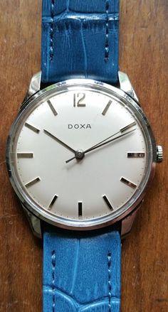 Doxa Dress horloge Mens Vintage 1960e van  Een prachtige en zeer mooie klassieke collectable gf 1960e van Doxa Dress horloge met een zeer schoon zilver white dial handen en markers. Het heeft een nieuwe blauwe lederen band en een zilveren vergulde gesp met een totale lengte van / _21.5 cm met inbegrip van de gesp. De metingen van de zaak zijn /-35 mm diameter (niet met inbegrip van de kroon) en /-40 mm van lug te sjouwen. Het kristal is nog steeds zeer leuke de mechanische 17 st. Doxa…