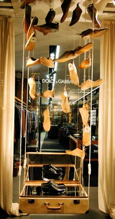 Dolce & Gabbana, Paris, men's window display with flying wooden shoe forms, Feb 2013. Nice use of mirrors inside the suitcase for more reflection and glow. #shoes #D