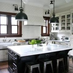 Simple black and white kitchen with industrial pendant lights