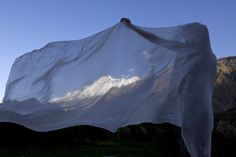 Woman with Veil Photograph by Andrea Francolini A woman adjusts her veil while the wind blows with Rakaposhi (7788m) in the background.