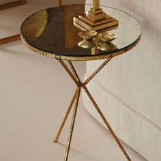 TRIOMPHE TRIPOD TABLE. An unobtrusive side table featuring slender legs in bronze metal and a circular antique mirrored top. #oka #mirrored