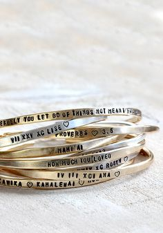 Personalized sterling silver and brass stacking cuff bracelets from Praxis Jewelry.