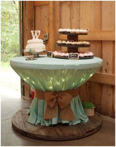 Upcycling and Wedding Decoration in one!.  Cover the top of wooden spool with icicle lights, and bunch table cloth with bungee cord on wedding days or any party at night!