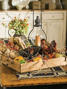 Country Sampler Gathered Together - Build a rustic centerpiece by combining a lantern, a redware rooster, and a pewter pitcher of greenery in a wood tray.  Add gourds and vines and a napkin for softness.