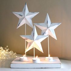 Charming seasonal tealight holder.Wonderful Christmas tealight holder of three whitewashed metal stars illuminated from beneath by tealights on a painted wooden base. Perfect christmas decoration for both a traditional or contemporary setting. Quite stunning on side tables or just as lovely placed on a window sill as a welcoming glow for visitors. Sold as a single tealight holder.Metal and wood.25.5cm x 16.5cm x 36cm